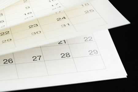 White calendar turning pages with dark black background using as time fly, season pass or reminder and appointment is coming concept.