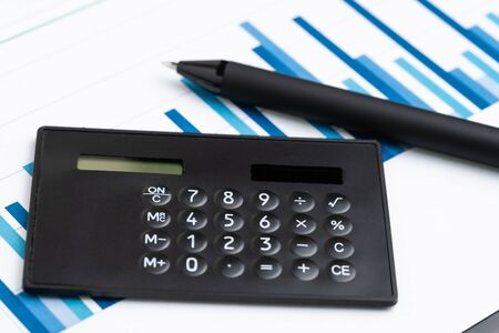 Black calculator with pen on blue bar graph reports using as accounting, financial analysis, profit and loss of company or stock market investment concept.
