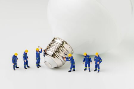 Business creative idea, sustainability power or energy generator concept, miniature people figurine engineer worker help building light bulb on white background.