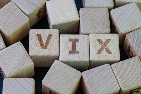Indice di volatilità, noto con il suo concetto di simbolo VIX, cubo di legno con alfabeto combina la parola VIX su sfondo nero lavagna. Archivio Fotografico