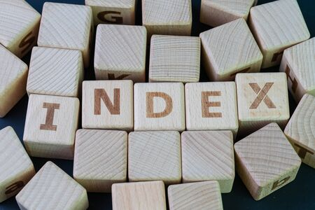Index fund, passive investing with low cost concept, cube wooden block with alphabet combine the word Index on black chalkboard background. Stock fotó