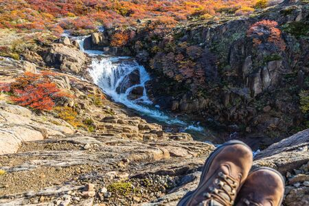 Beautiful view of waterfall in front of Fitz roy mountains with colorful red orange leaves tree in sunny day with the foreground of trekking shoes, autumn, El Chalten, south Patagonia, Argentina.