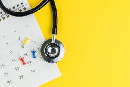 Medical and health care calendar, reminder, schedule or appointment concept, doctors stethoscope, thumbtack pin on white clean calendar with date on solid yellow background with copy space. Stock fotó