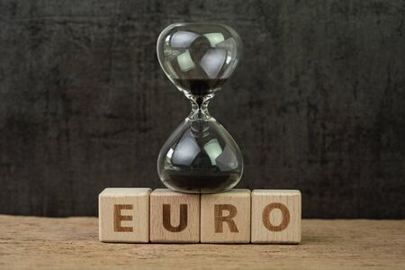 Euro countdown after Brexit referendum to withdraw from Europe, hourglass or sandglass on wooden cube block with alphabet building the word Euro on wood table, dark black background. Banco de Imagens