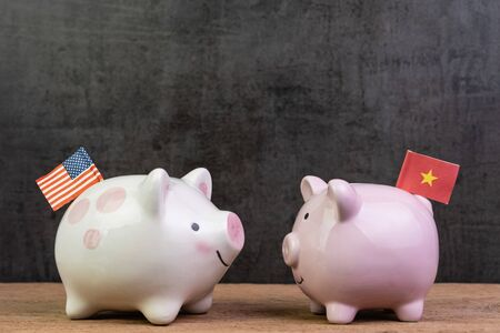 US and China trade war or tariffs negotiation concept, piggy bank with United state national flag face to face with one with China flag on wood table dark background with copy space.