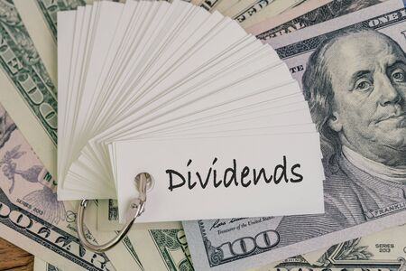 Dividends, return or earning that pay from stock or mutual fund investing concept, lot of paper notes with handwriting word Dividends on pile of US Dollar banknotes money.