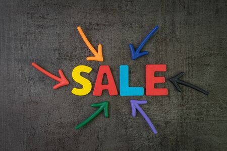 Sale, discount in price of good and services concept, multi color arrows pointing to the word Sale at the center of black cement chalkboard wall. Stock fotó