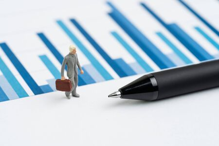 Business performance, KPI, key performance indicator or company revenue or profit on management, miniature people businessman leader in suit carrying suitcase on bar graph report with pen. Stock fotó