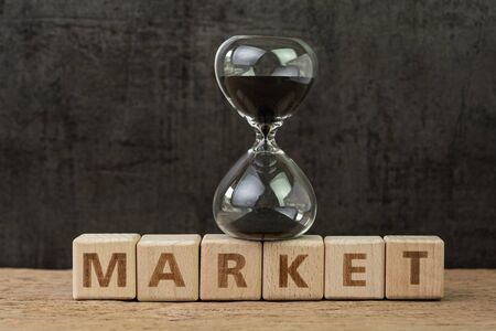 Time countdown for stock market, fluctuation on market, hourglass or sandglass on wooden cube block with alphabet building the word Market on wood table, dark black background.