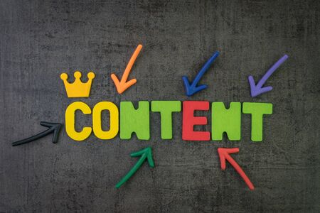 Content is king in modern advertising concept, multi color arrows pointing to the word Content at the center of black cement chalkboard wall.