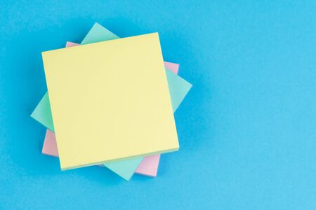 Stack of sticky notes on solid blue background with pink, blue and yellow on top with copy space for writing message using as memo, reminder or business idea and important quote. Stock fotó