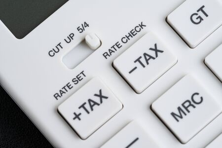 White calculator buttons such selective focus on tax minus and tax plus on black leather using as taxation, maths, investment banking and accounting.