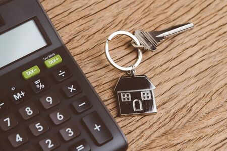 Mortgage calculation or buy and sell house, property and real estate, home key with house keyring or keychain with black calculator on wooden table.