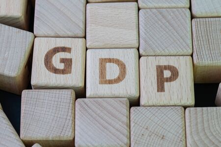 Gross domestic product (GDP), a monetary measure of the market value of country goods and services concept, cube wooden block with alphabet combine the word GDP on black chalkboard background.