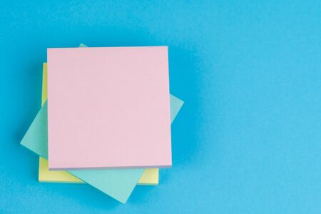Stack of sticky notes on solid blue background with yellow, blue and pink on top with copy space for writing message using as memo, reminder or business idea and important quote.