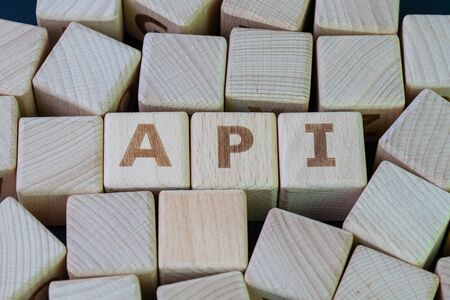 Application Programming Interface (API) middleware for applications to communicate with another concept, cube wooden block with alphabet combine the word API on black chalkboard background.