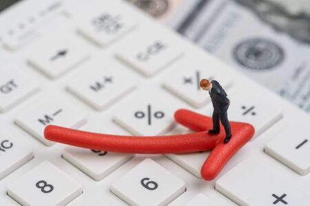 Economische recessie, berenbeurs of financiële crisisconcept, miniatuurzakenman die op rode pijl naar beneden wijst op witte rekenmachine met achtergrond van Amerikaanse dollarbankbiljetgeld. Stockfoto