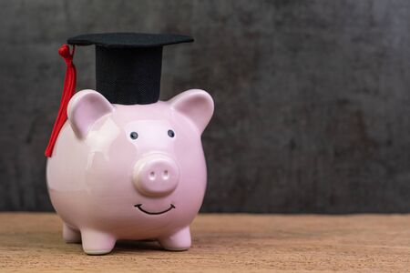 Sonriendo alcancía rosa con sombrero graduado en mesa de madera con fondo negro oscuro y espacio de copia, fondo de educación, becas, costo universitario y gasto o ahorro para concepto de préstamo estudiantil. Foto de archivo