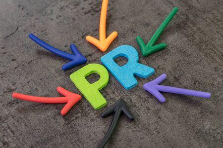 PR, concept de relations publiques, flèches multicolores pointant vers l'abréviation PR au centre du mur de tableau en ciment noir, l'activité pour promouvoir l'entreprise.