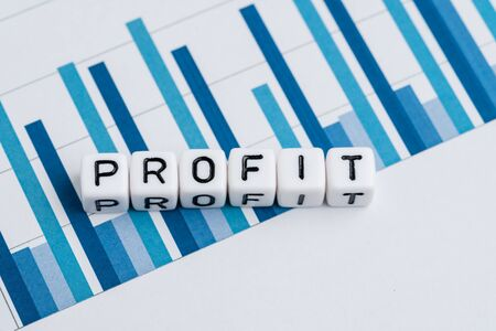 Profit, revenue for company or positive return for investment concept, small cube block with alphabets building the word Profit on blue yearly bar chart and graph reports.