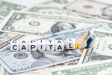 Miniature people man pulling forklift with cube small block building the word Capital on pile of US Dollar banknote money using as capital market, capitalism or global financial concept.