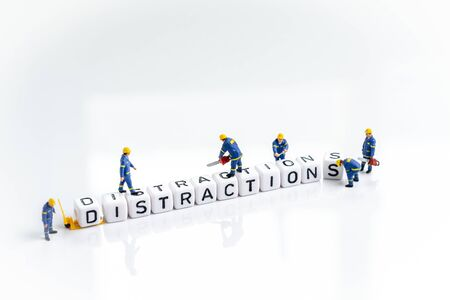 Eliminate distractions that draw attention to losing focus concept, miniature people man working on cube small block building the word Distractions on solid white background. Stock Photo