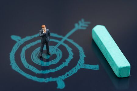 Miniature businessman standing on chalk drawing bullseye target with pastel green chalk on blackboard using as achieve business goal, career path plan or motivation for job and work target. 版權商用圖片