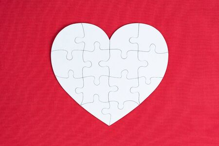 Valentines day, combination of love, jigsaw of love, family or pieces of love concept, top view of white pieces jigsaw combine lovely heart shape on red background.