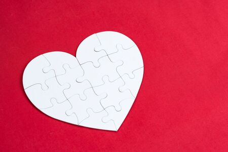 Valentines day, combination of love, jigsaw of love, family or pieces of love concept, white pieces jigsaw combine lovely heart shape on red background with copy space.