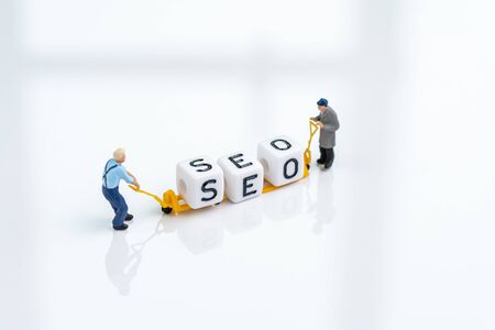 SEO, Search Engine Optimization, website search result advertising concept, miniature people man pulling forklift with cube small block building the word SEO on solid white background.