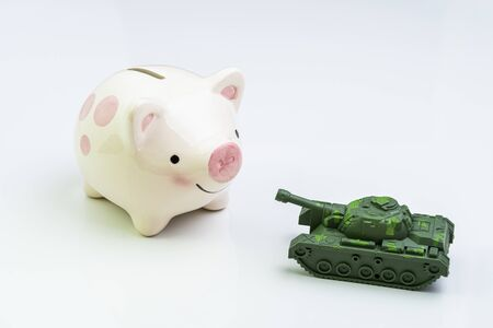 Trade war, economic impact of war or trading power concept, miniature tank toy pointing the gun at smiling pink piggy bank on white background.