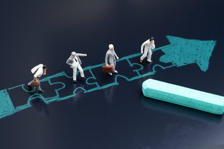 Business success with teamwork, job and career path or partnership concept, miniature people businessmen standing in drawing jigsaw with arrow in same direction with chalk on blackboard.