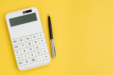 Cost, expense calculation or finance and investment concept, white clean modern calculator with pen on solid yellow background with copy space.