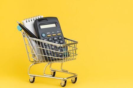 Shopping list, check out and payment or expense calculation concept, calculator and small note with pen for writing list in miniature shopping cart or shop trolley on yellow copy space background.