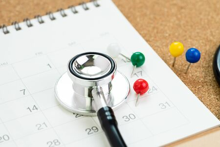 Stethoscope with colorful thumbtack or pushpin on white calendar, schedule or appointment for medical exam or meet the doctor for health check up concept. 免版税图像