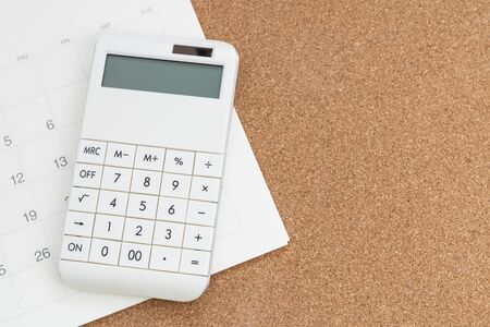 Flat lay or top view of white calculator on calendar on wooden background with copy space, tax schedule time, year or monthly financial expense, cost or investment planning. 免版税图像