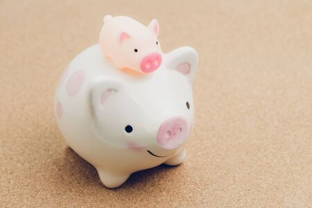 Small cute piggy bank on his piggy bank mom on wooden background using as money, finance, saving and investment concept.