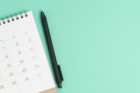 Flat lay or top view of white clean calendar with black pen on pastel green background with copy space, schedule or project milestone and reminder, business meeting planning concept.
