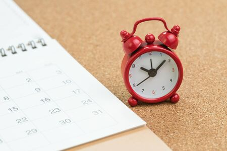 Red alarm clock with white calendar on wooden table background, schedule for vacation, reminder for business appointment or deadline for business project. 免版税图像