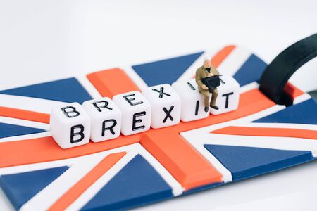 Miniature sad man sit on cube block with alphabets building the word BREXIT on union jack UK flag with white copy space background using as United Kingdom leaving EU European Union concept.