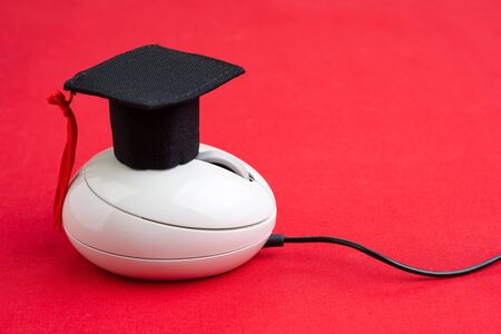Online course, e-learning or internet study via website and online teaching concept, graduation hat on computer mouse on red background.