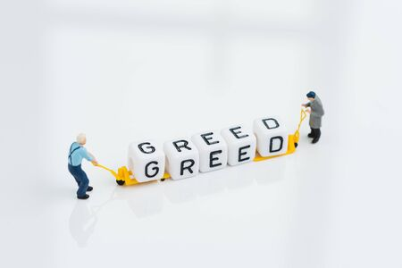 Greed and fear index in stock market,  investment or behavioral finance concept, miniature man pulling forklift with cube block building the word GREED on clean white background.
