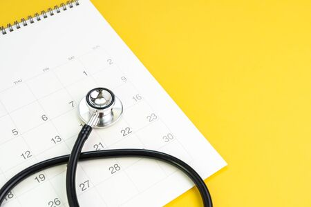 Stethoscope on clean calendar with copy space to put month and year, reminder for annual health checkup, medical appointment or examination schedule or remind to meet the doctor concept. 免版税图像