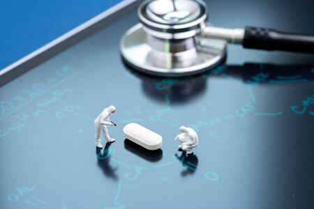 Miniature people doctors working on white pill tablet on chemical compound on blackboard with the headline COVID-19 using as Corona virus medicine or vaccine, 2019 nCOV flu outbreak cure concept.