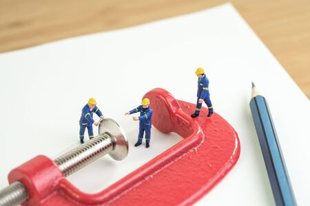Miniature worker working with red squeezed clamp on notebook with pencil using as budget or financial squeezed, workbench, carpenter an d tools concept.