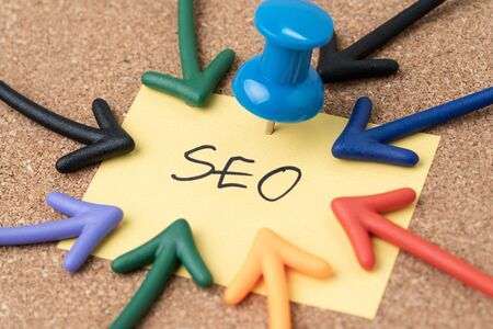 SEO Search Engine Optimization, keywords marketing to drive traffic to website concept, Thumbtack pushpin with multi arrows pointing to small paper note written the word SEO. 免版税图像