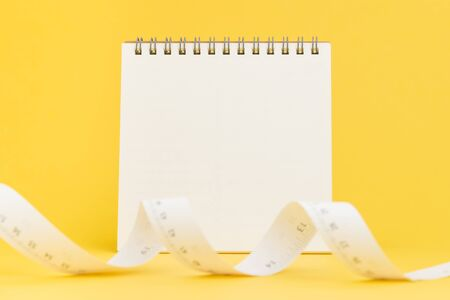 Nutrition diet and loss weight reminder, tailer designer or measure tool for furniture and house concept, blank desktop paper area to put text with white paper measuring tape on yellow background.