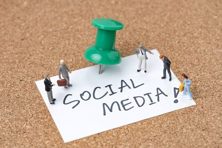 Social media people or social network concept, miniature people men and women standing on small paper note written the word Social Media pin with thumb tack or pushpin on pin board.