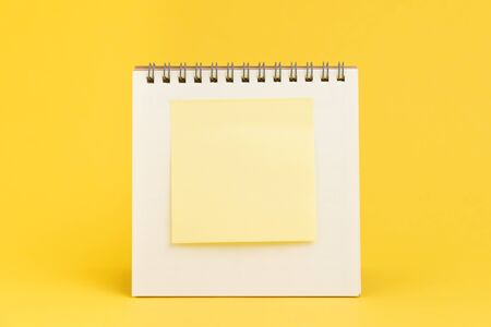 Blank sticky note with copy space to put text on desktop calendar on yellow background using as reminder, important message or memo concept.