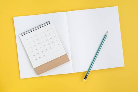 Timeline planning, checklist or business plan with calendar date concept, pencil on blank page note book paper with calendar on yellow background. Stock fotó